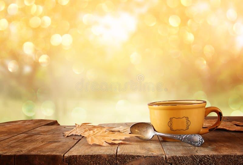 Μπροστινή εικόνα του φλυτζανιού καφέ πέρα από τα ξύλινα φύλλα πινάκων και φθινοπώρου μπροστά από το φθινοπωρινό υπόβαθρο ηλιοβασι στοκ εικόνες