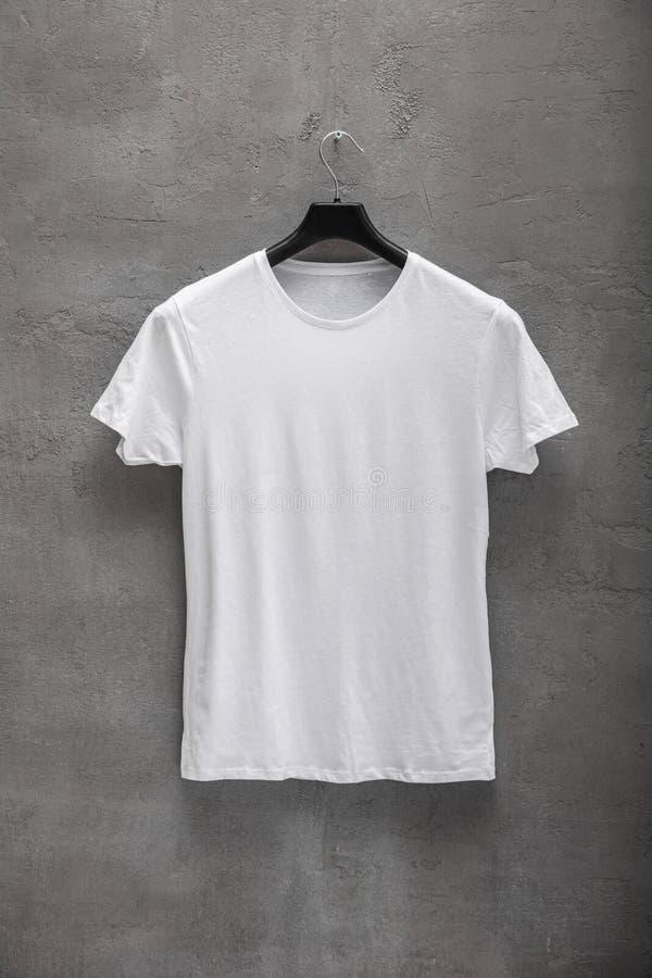 Μπροστινή πλευρά της αρσενικής άσπρης μπλούζας βαμβακιού σε μια κρεμάστρα και ενός συμπαγούς τοίχου στο υπόβαθρο στοκ φωτογραφία με δικαίωμα ελεύθερης χρήσης