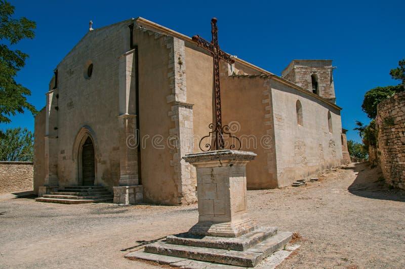 Μπροστινή πρόσοψη της εκκλησίας πετρών μια ηλιόλουστη ημέρα με την κρουαζιέρα πρώτου πλάνου, σε Menerbes στοκ εικόνες με δικαίωμα ελεύθερης χρήσης