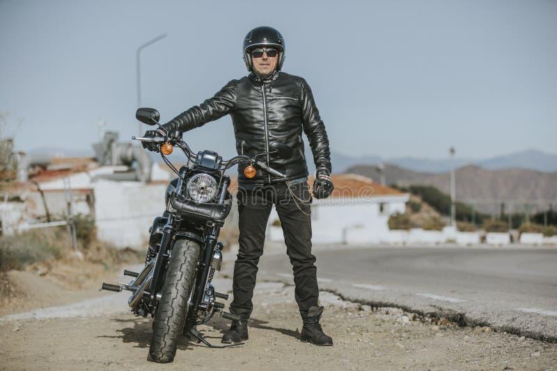 Μπροστινό πορτρέτο του ατόμου στα μαύρα ενδύματα που θέτουν κοντά στη μοτοσικλέτα του στοκ φωτογραφίες με δικαίωμα ελεύθερης χρήσης