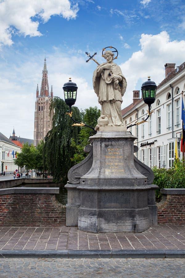 Μπρυζ, Βέλγιο - 16 Αυγούστου 2013: Άγαλμα του Johannes Nepomucenus και ο πύργος εκκλησιών ενάντια στο μπλε ουρανό στη Μπρυζ στοκ εικόνα