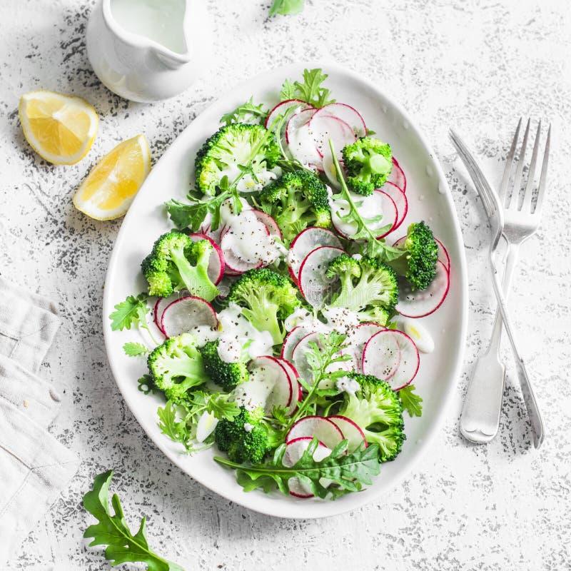 Μπρόκολο φρεσκάδας και σαλάτα ραδικιών με τη σάλτσα γιαουρτιού σε ένα ελαφρύ υπόβαθρο, τοπ άποψη Εύγευστη υγιής χορτοφάγος έννοια στοκ εικόνα με δικαίωμα ελεύθερης χρήσης