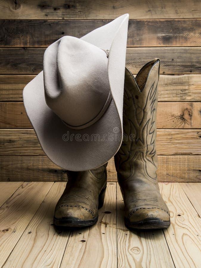 Μπότα κάουμποϋ και δυτικό καπέλο σε ξύλινο στοκ φωτογραφία