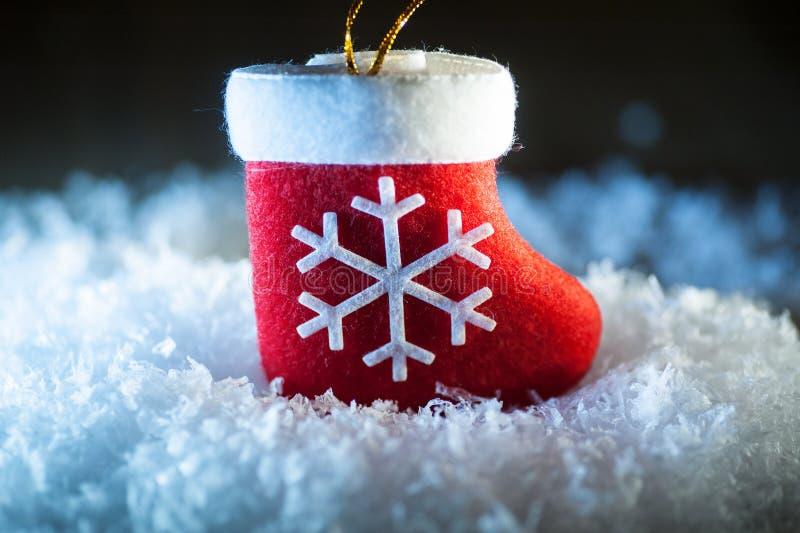 Μπότα κόκκινου Santa με snowflake στο χιόνι στοκ εικόνες