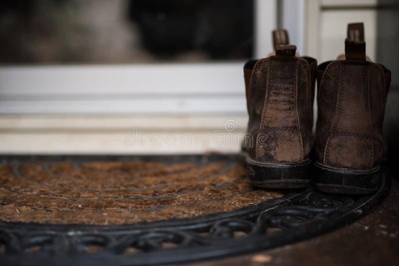 Μπότες αγροτών που αφήνονται από την πόρτα στοκ εικόνες