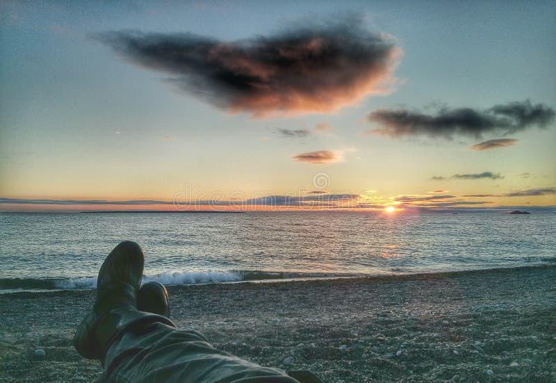 Μπότες και εσώρουχα μοτοσικλετών που προσέχουν το ηλιοβασίλεμα στοκ φωτογραφίες