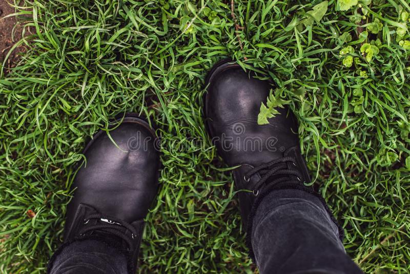 Μπότες μαύρων γυναικών στην πράσινη χλόη στοκ εικόνες
