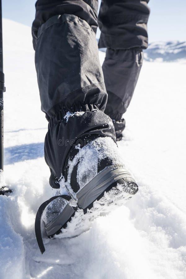 Μπότες οδοιπορίας χειμερινών βουνών στην πορεία χιονιού στοκ εικόνες