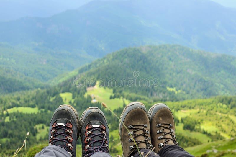 Μπότες πεζοπορίας της ταξιδιωτικής συνεδρίασης στην κορυφή υψηλών βουνών στοκ φωτογραφίες