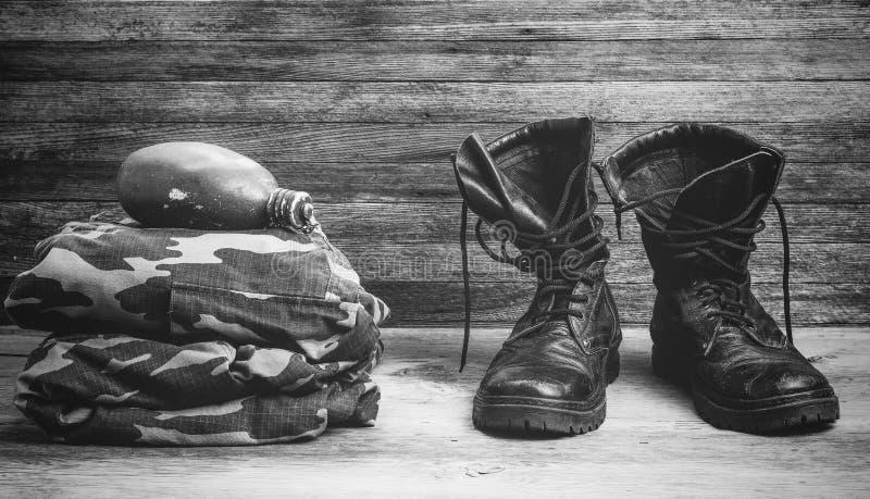 Μπότες, στρατιωτική στολή και φιάλη των παλαιών μαύρων δέρματος για το νερό σε μια ξύλινη κινηματογράφηση σε πρώτο πλάνο μπροστιν στοκ εικόνα με δικαίωμα ελεύθερης χρήσης