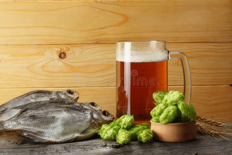 Μπύρα γυαλιού με τα αποξηραμένα ψάρια στο ελαφρύ ξύλινο υπόβαθρο Έννοια ζυθοποιείων μπύρας Ανασκόπηση μπύρας στοκ εικόνα