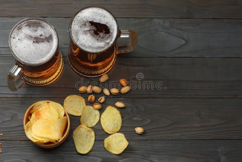 Μπύρα γυαλιού με τα τσιπ φυστικιών και πατατών στο σκοτεινό ξύλινο υπόβαθρο Έννοια ζυθοποιείων μπύρας Ανασκόπηση μπύρας Τοπ άποψη στοκ εικόνα με δικαίωμα ελεύθερης χρήσης