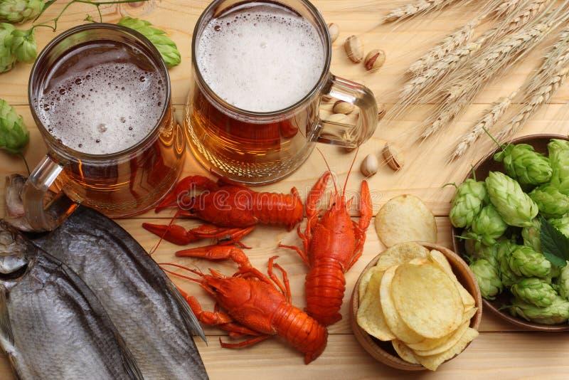 Μπύρα γυαλιού με τους αστακούς, τους κώνους λυκίσκου και τα αυτιά σίτου στο ελαφρύ ξύλινο υπόβαθρο Έννοια ζυθοποιείων μπύρας Ανασ στοκ φωτογραφίες