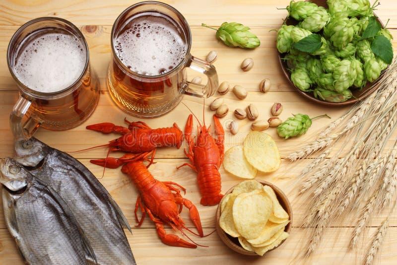 Μπύρα γυαλιού με τους αστακούς, τους κώνους λυκίσκου και τα αυτιά σίτου στο ελαφρύ ξύλινο υπόβαθρο Έννοια ζυθοποιείων μπύρας Ανασ στοκ εικόνα