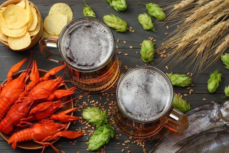 Μπύρα γυαλιού με τους αστακούς, τα αποξηραμένους ψάρια και τους κώνους λυκίσκου στο σκοτεινό ξύλινο υπόβαθρο Έννοια ζυθοποιείων μ στοκ εικόνες