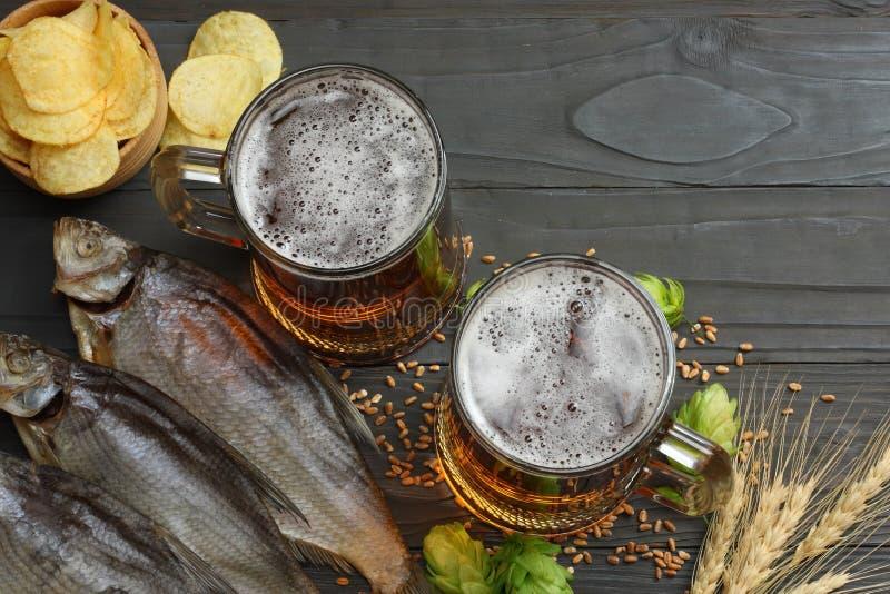 Μπύρα γυαλιού με τους κώνους λυκίσκου, τα αποξηραμένα ψάρια και τα αυτιά σίτου στο σκοτεινό ξύλινο υπόβαθρο Έννοια ζυθοποιείων μπ στοκ φωτογραφίες