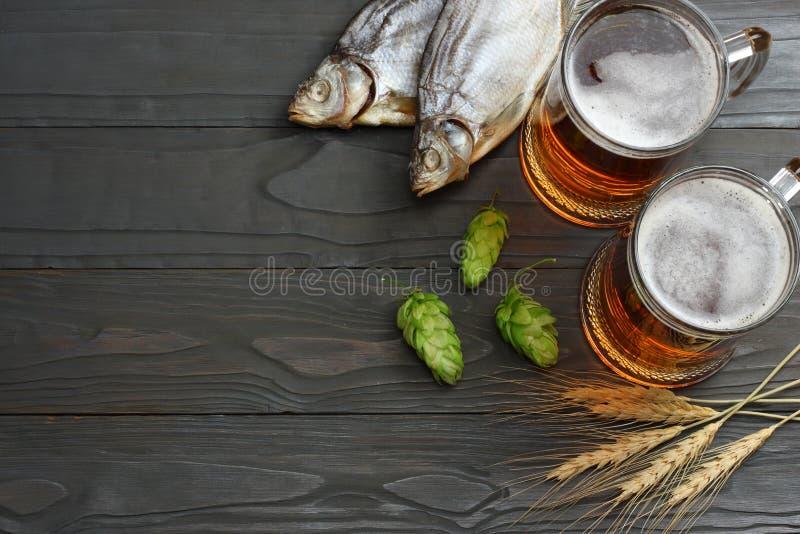 Μπύρα γυαλιού με τους κώνους λυκίσκου, τα αποξηραμένα ψάρια και τα αυτιά σίτου στο σκοτεινό ξύλινο υπόβαθρο Έννοια ζυθοποιείων μπ στοκ εικόνες με δικαίωμα ελεύθερης χρήσης