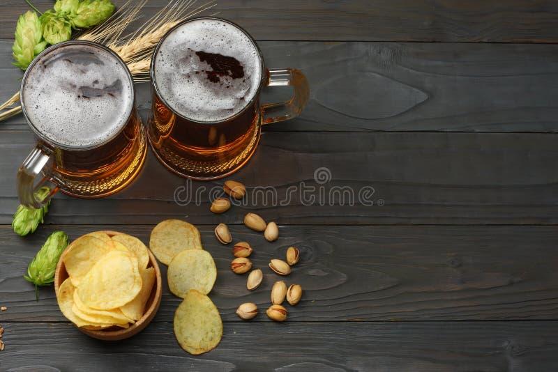 Μπύρα γυαλιού με τους κώνους λυκίσκου, τα αυτιά φυστικιών και σίτου στο σκοτεινό ξύλινο υπόβαθρο Έννοια ζυθοποιείων μπύρας Ανασκό στοκ εικόνα με δικαίωμα ελεύθερης χρήσης