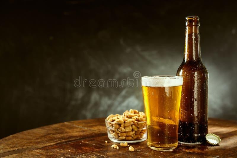 Μπύρα και φυστίκια σε έναν παλαιό ξύλινο πίνακα φραγμών στοκ εικόνες