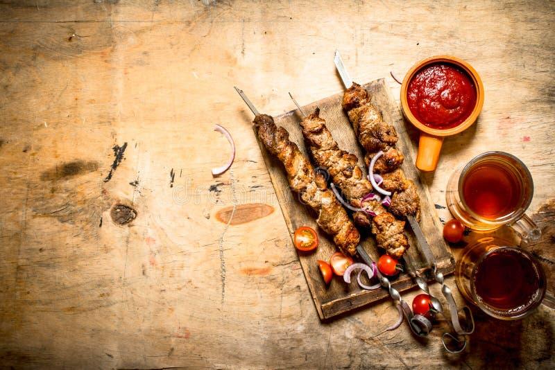 Μπύρα με το χοιρινό κρέας Shish kebab και τις ντομάτες στοκ εικόνα