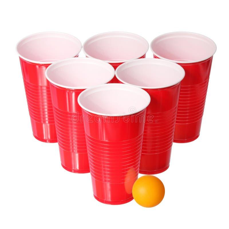 Μπύρα pong. Κόκκινα πλαστικά φλυτζάνια και πορτοκαλιά σφαίρα αντισφαίρισης που απομονώνονται στο λευκό. Κινηματογράφηση σε πρώτο π στοκ φωτογραφία με δικαίωμα ελεύθερης χρήσης