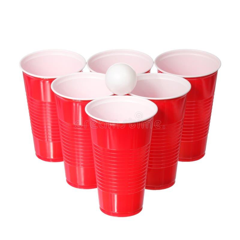 Μπύρα pong. Κόκκινες πλαστικές φλυτζάνια και σφαίρα αντισφαίρισης που απομονώνεται στοκ φωτογραφίες με δικαίωμα ελεύθερης χρήσης