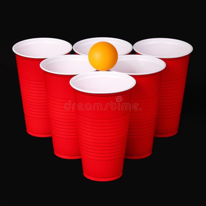 Μπύρα pong. Τα κόκκινα πλαστικά φλυτζάνια και ο πορτοκαλής πίνακας η σφαίρα πέρα από το Μαύρο στοκ φωτογραφία