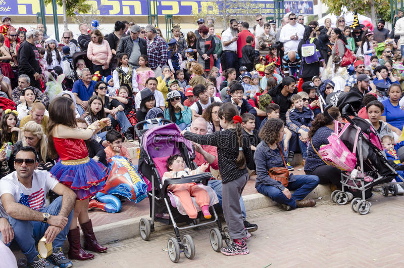Μπύρα-Sheva, ΙΣΡΑΗΛ - 5 Μαρτίου 2015: Γονείς με το ακροατήριο παιδιών - καθίστε και προσέξτε την απόδοση στην οδό - Purim στοκ εικόνα με δικαίωμα ελεύθερης χρήσης