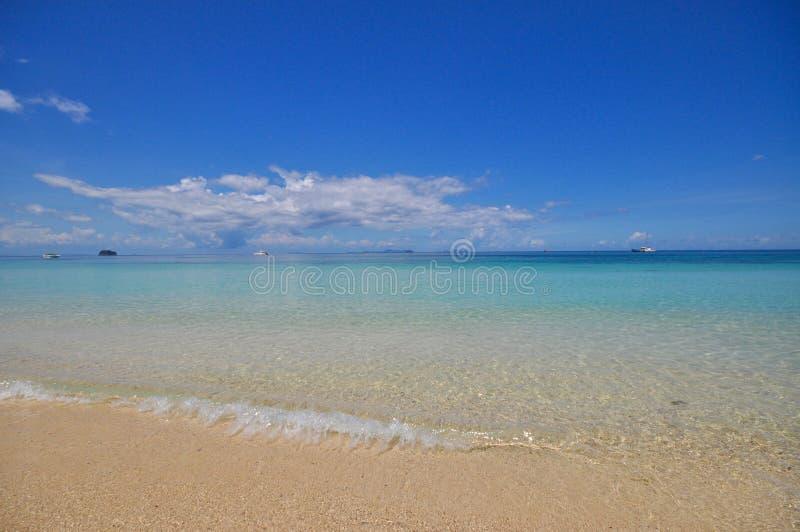 Μπλε ήρεμη θάλασσα με την άσπρη άμμο στοκ φωτογραφίες