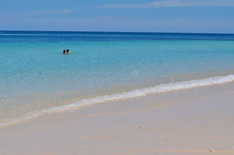 Μπλε ήρεμη θάλασσα με την άσπρη άμμο στοκ εικόνες