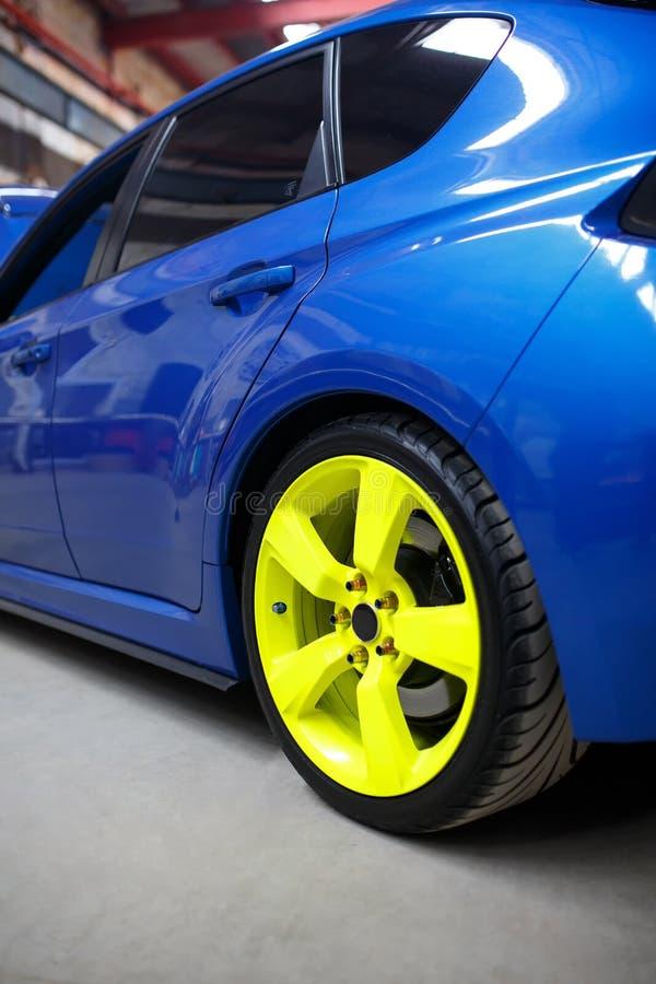 Μπλε αυτοκίνητο με την πράσινη ρόδα κραμάτων εσωτερική στοκ εικόνα