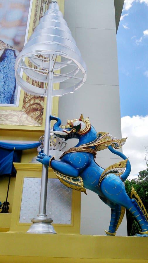 Μπλε βασιλικό λιοντάρι που κρατά την τοποθετημένη στη σειρά ομπρέλα στοκ εικόνες με δικαίωμα ελεύθερης χρήσης