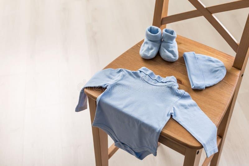 Μπλε ενδυμασία μωρών στην καρέκλα στοκ φωτογραφίες