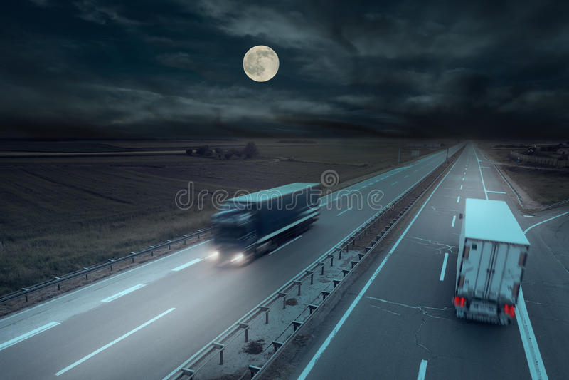 Μπλε και άσπρο φορτηγό στη θαμπάδα κινήσεων στα μεσάνυχτα στοκ εικόνες