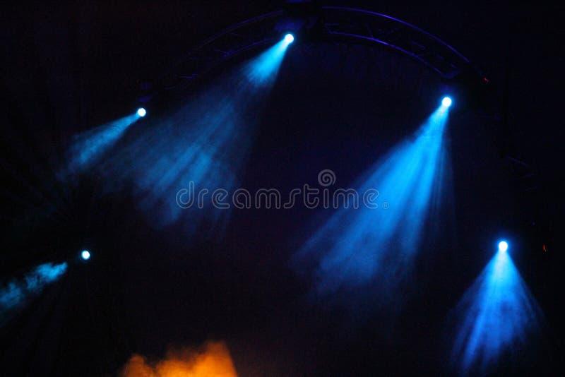Μπλε και κίτρινος χρωματισμένος ελαφρύς παρουσιάζει πέρα από τη σκηνή συναυλίας στοκ εικόνα