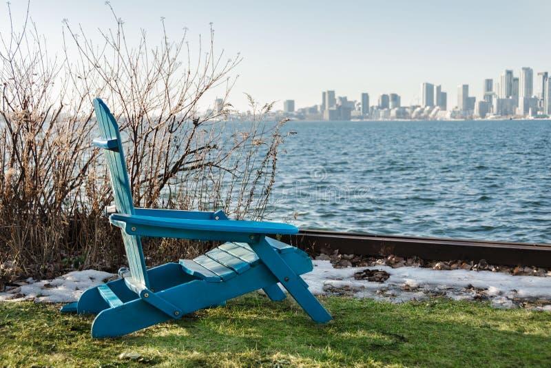Μπλε καρέκλα στην προκυμαία με τις απόψεις της πόλης στο sprin στοκ φωτογραφία με δικαίωμα ελεύθερης χρήσης
