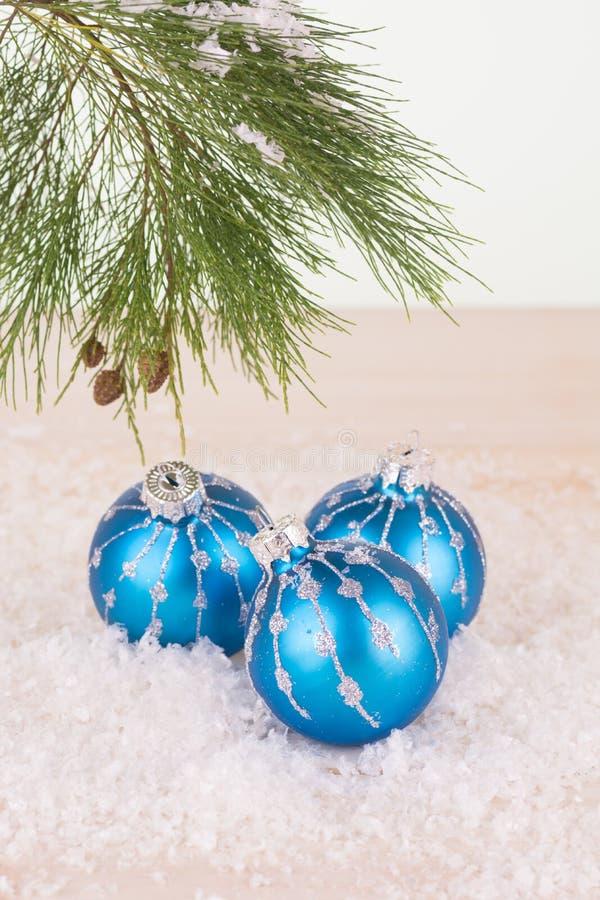 Μπλε μπιχλιμπίδια Χριστουγέννων snowflakes και τον κλάδο δέντρων πεύκων στοκ φωτογραφία