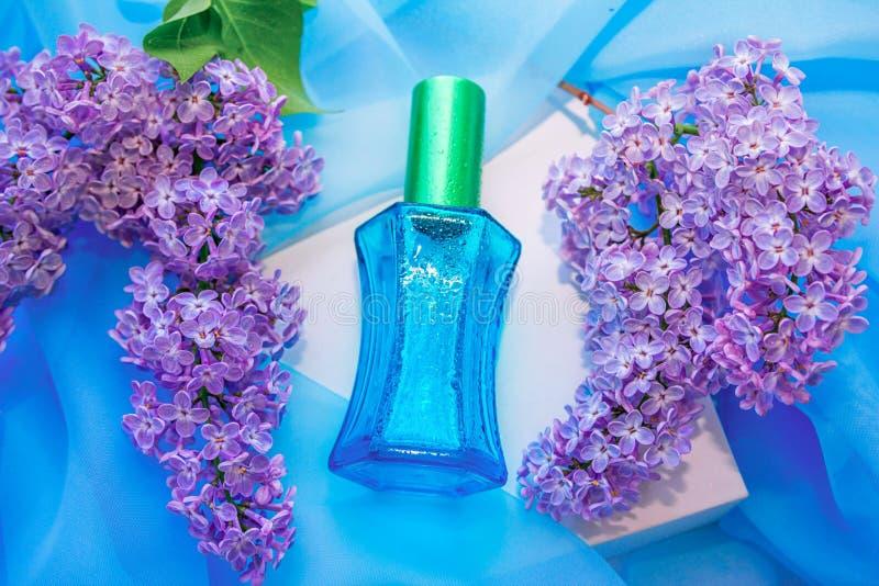 Μπλε μπουκάλι αρώματος γυαλιού και ιώδη λουλούδια στοκ φωτογραφία