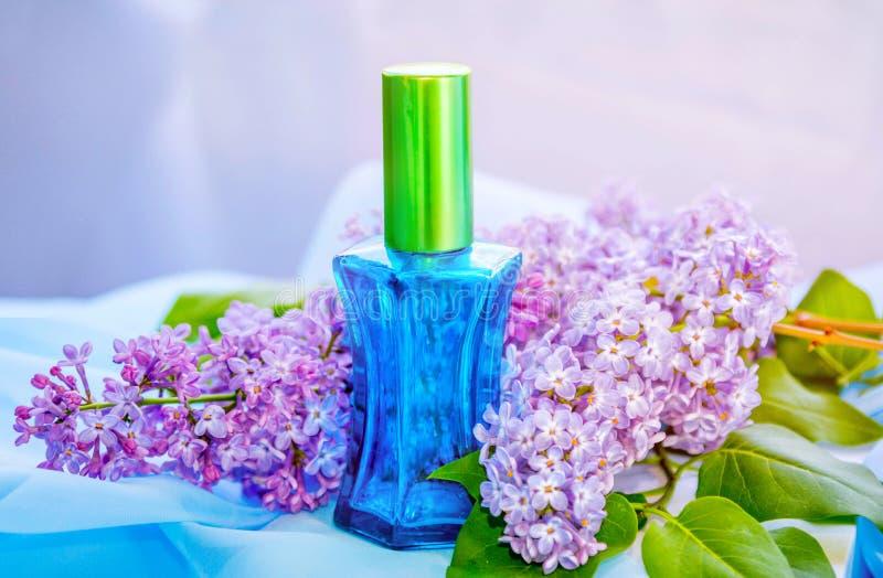 Μπλε μπουκάλι αρώματος γυαλιού και ιώδη λουλούδια στοκ φωτογραφία με δικαίωμα ελεύθερης χρήσης