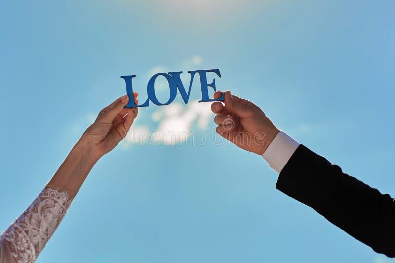 Μπλε ξύλινη αγάπη λέξης στα χέρια του γαμήλιου ζεύγους σε έναν μπλε ουρανό στοκ εικόνα με δικαίωμα ελεύθερης χρήσης
