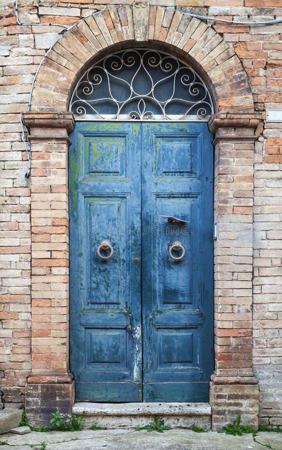 Μπλε ξύλινη πόρτα με την αψίδα στον παλαιό τουβλότοιχο στοκ φωτογραφίες