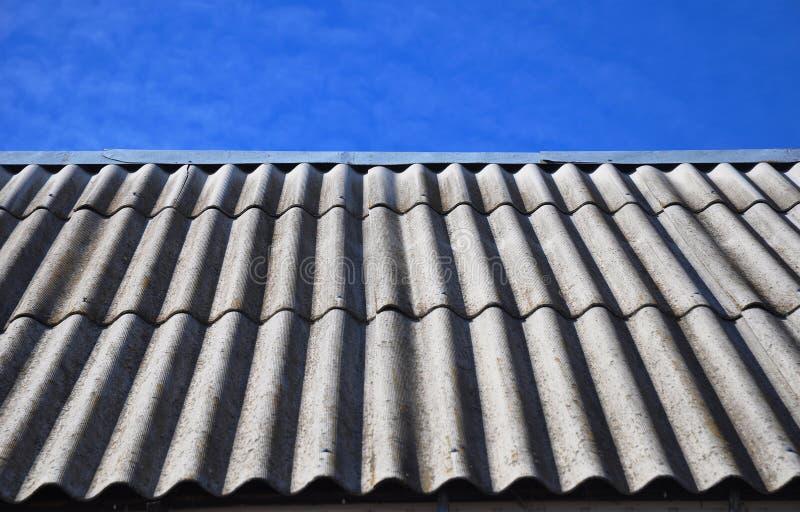 Μπλε ουρανός πέρα από τα επικίνδυνα κεραμίδια στεγών αμιάντων παλαιά στοκ φωτογραφίες με δικαίωμα ελεύθερης χρήσης