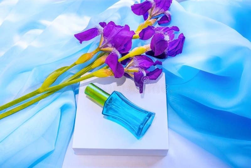 Μπλε λουλούδια μπουκαλιών και ίριδων αρώματος γυαλιού στοκ εικόνες