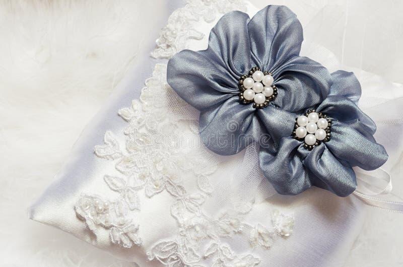 Μπλε λουλούδια στο μαξιλάρι σατέν στοκ εικόνα