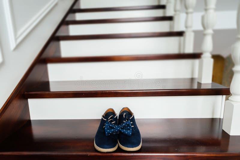Μπλε παπούτσια σουέτ και ένας μπλε διαστιγμένος δεσμός τόξων στα σκαλοπάτια στοκ φωτογραφία