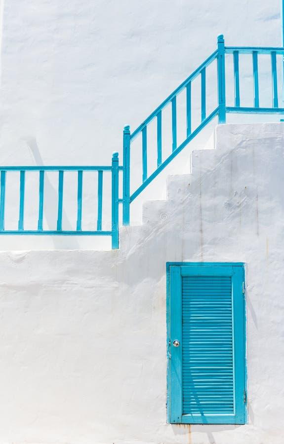 Μπλε πόρτα στον άσπρο τοίχο και μπλε σκάλα στοκ φωτογραφία με δικαίωμα ελεύθερης χρήσης