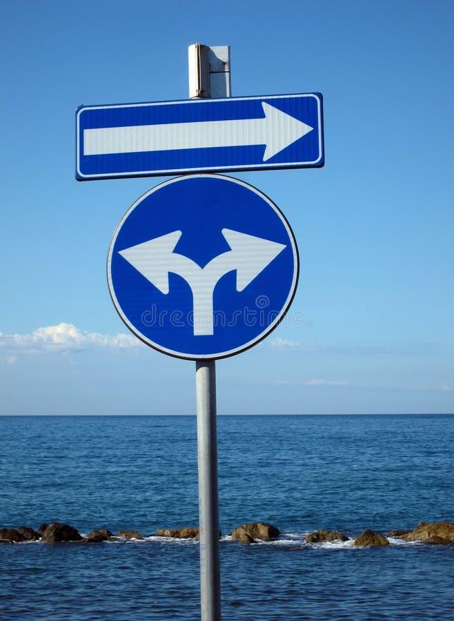 Μπλε σημάδια για τις κατευθύνσεις στο υπόβαθρο με τη θάλασσα και τον ουρανό στοκ φωτογραφία