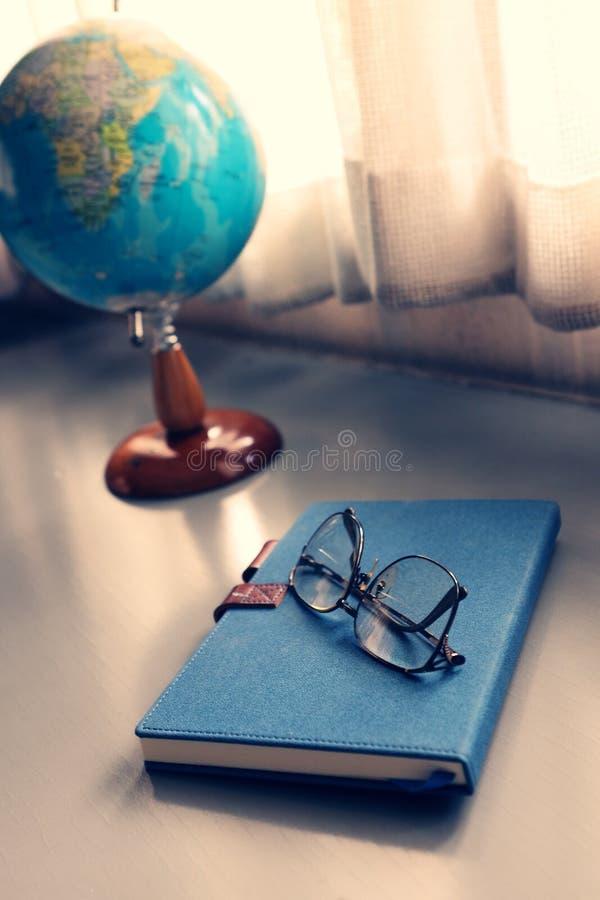 Γυαλιά στο σημειωματάριο με τη σφαίρα στοκ φωτογραφία με δικαίωμα ελεύθερης χρήσης