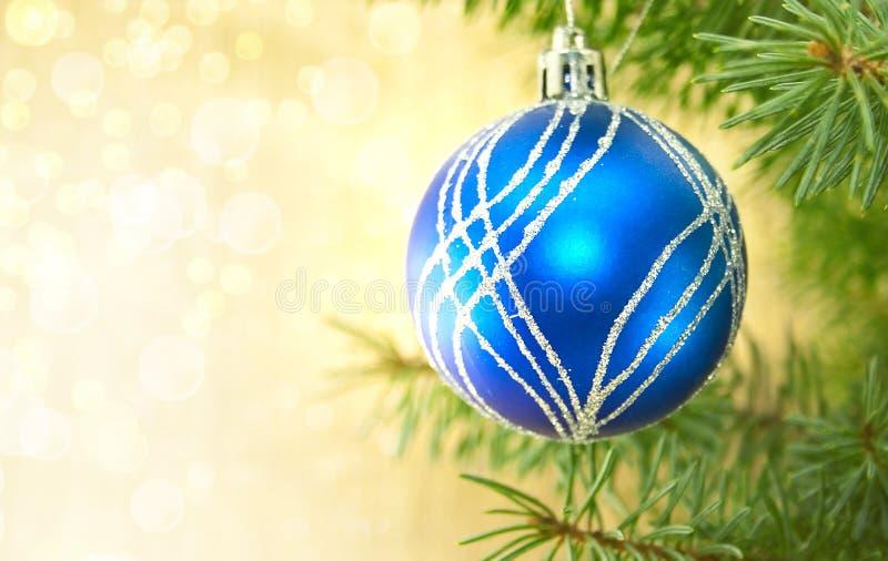 Μπλε σφαίρα Χριστουγέννων και πράσινο δέντρο στο λαμπρό υπόβαθρο με το αντίγραφο στοκ εικόνα