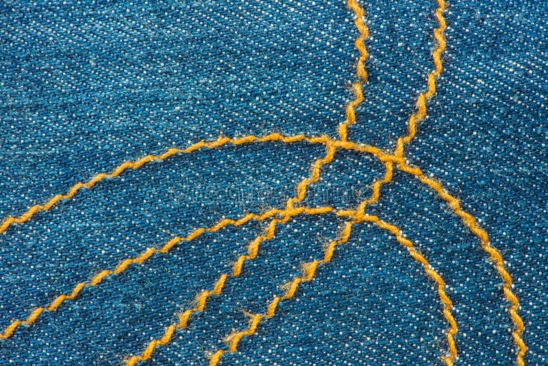 Μπλε τζιν Jean και κίτρινο υπόβαθρο σύστασης ραφών στοκ φωτογραφία με δικαίωμα ελεύθερης χρήσης